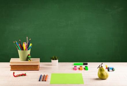 School supplies on a desk in front of an empty chalkboard.