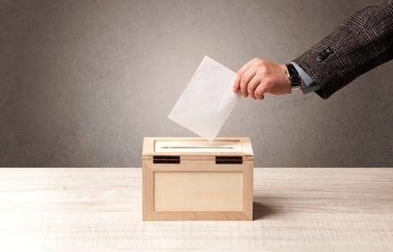 Hand casting a vote in a ballot box.