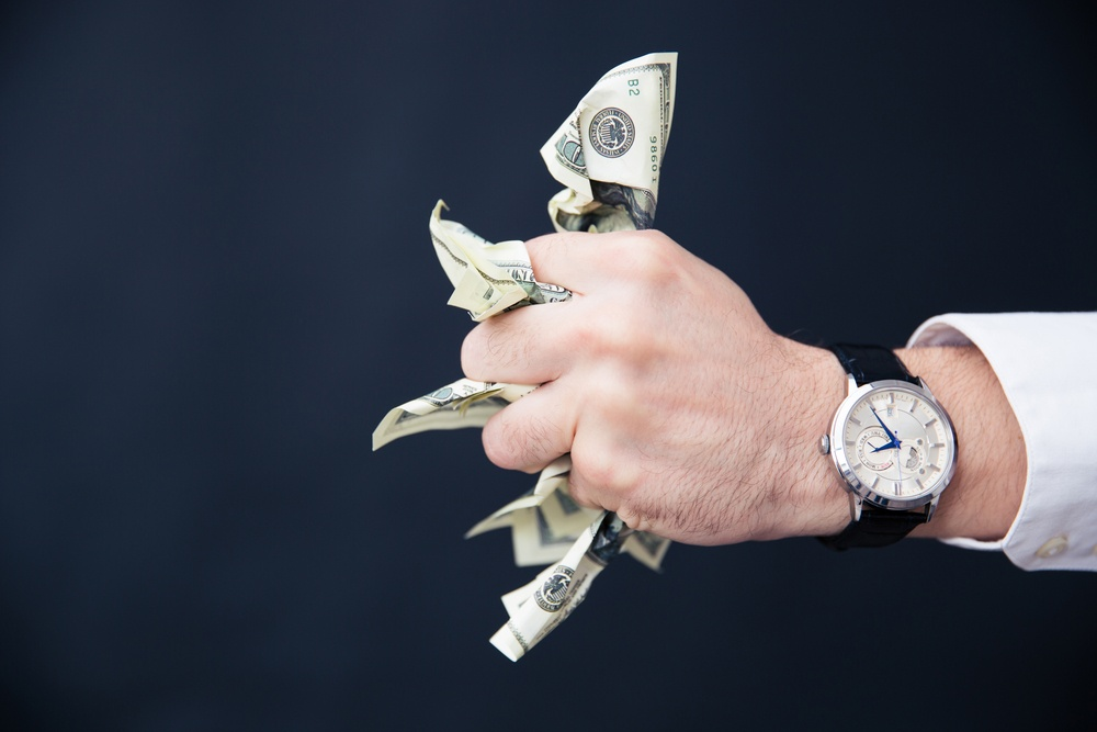 Closeup image of a businessman hand holding bills of US dollar in fist