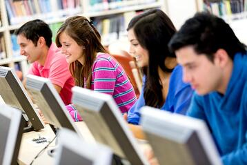 Group of young people studying at the library using computers.jpeg