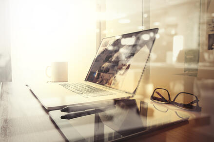 Laptop and glasses sit on a desk in a bright, somewhat blurry, sun-filled office.