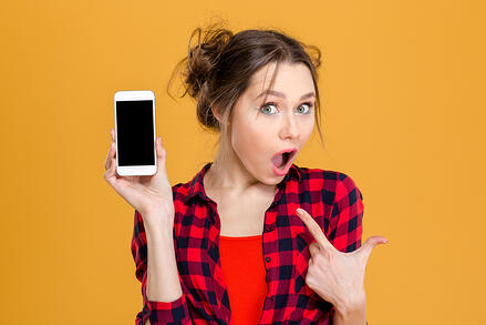 Portrait of a young amazed woman showing blank smartphone screen over yellow background. Focus on smartphone