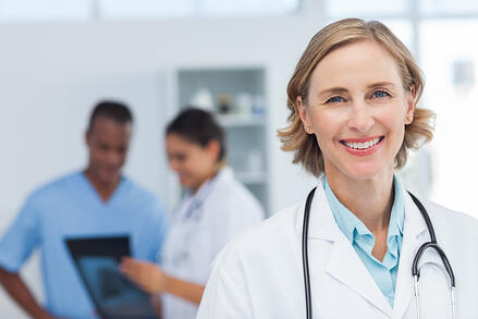 Smiling doctor with medical team working behind her.