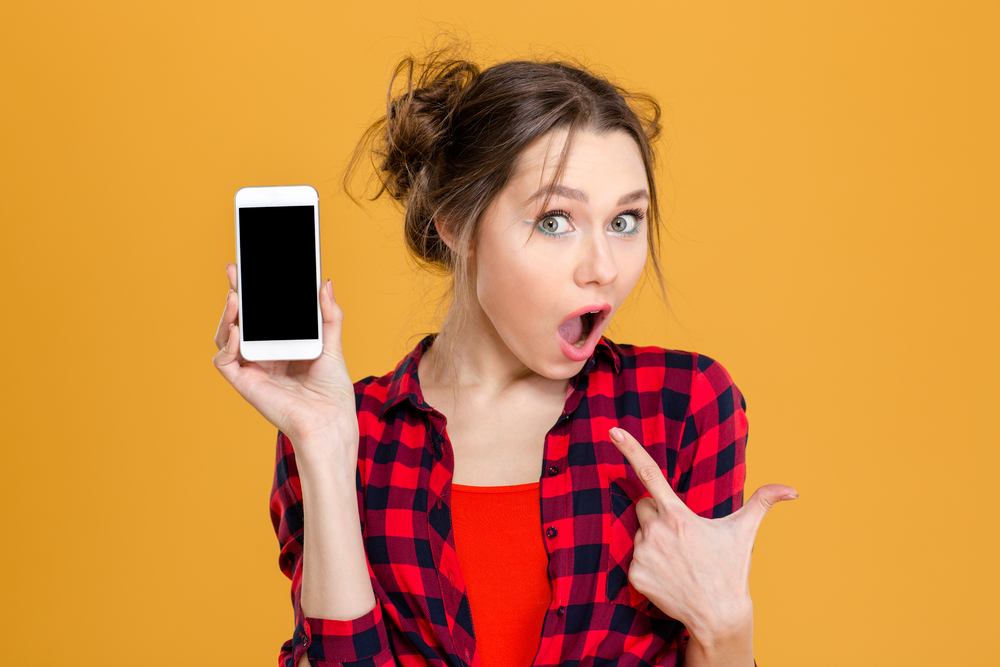 Young woman, amazed, holding and pointing to smartphone.