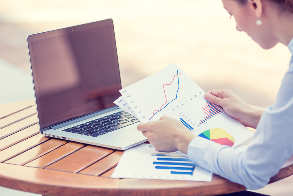 Business person in front of a laptop, reviewing printed charts and graphs
